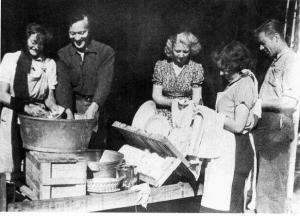 Ryhmä miehiä ja naisia pesemässä ja kuivaamassa tiskejä.