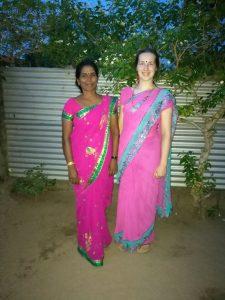 Suomalainen ja srilankalainen nainen vaaleanpunaisissa sareissa vierekkäin seisomassa.