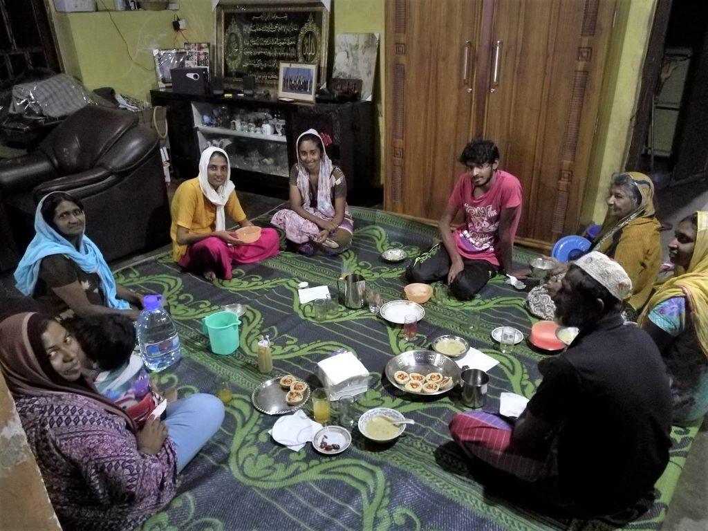 Ihmiset istuvat ringissä matolla ja ruoka-astiat keskellä