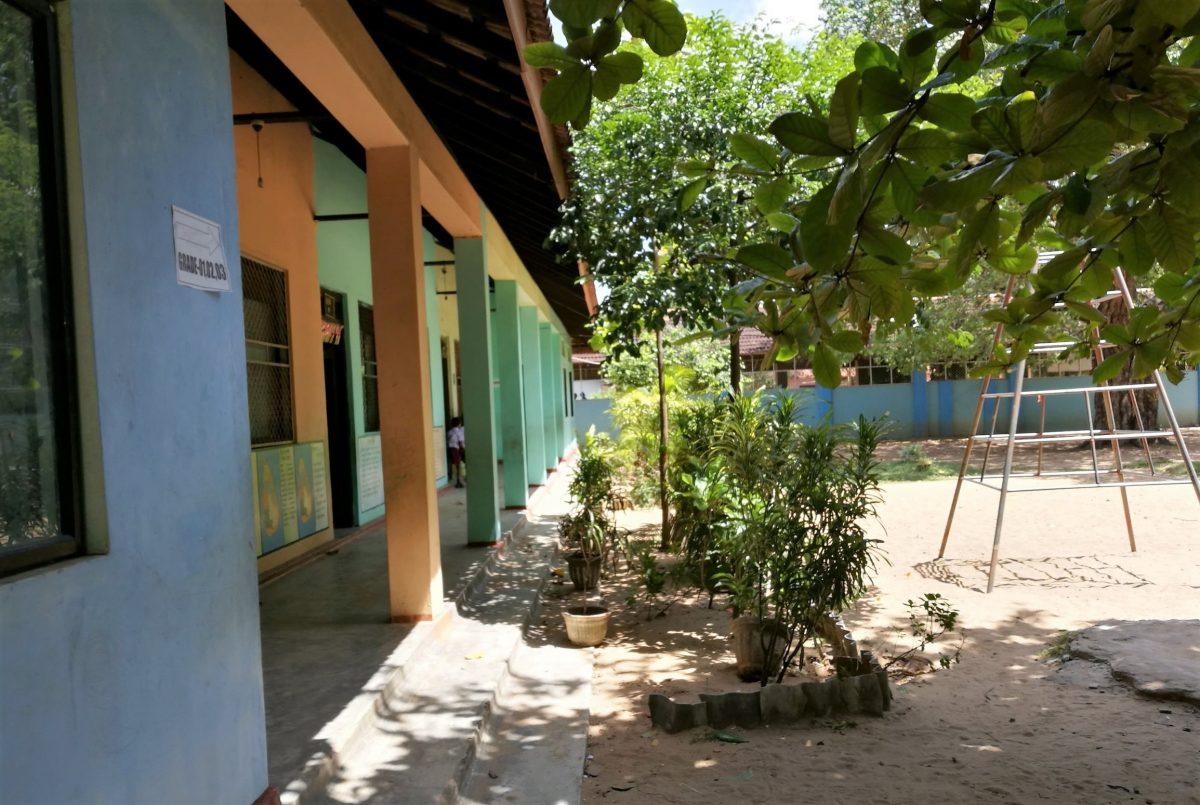 Koulun seinämä jossa kulkee pylväikkö ja pihalla kasveja ja kiipeilyteline.