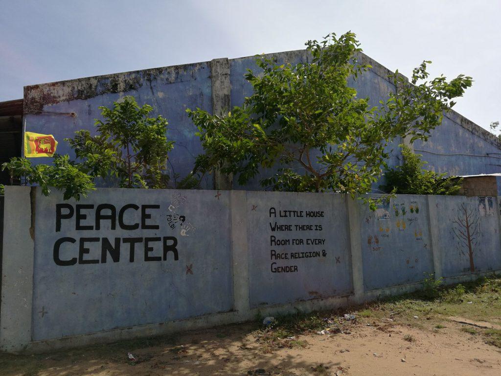 """Sininen rakennus puiden ja sinisen aidan takana. Aidassa lukee """"Peace Center""""."""