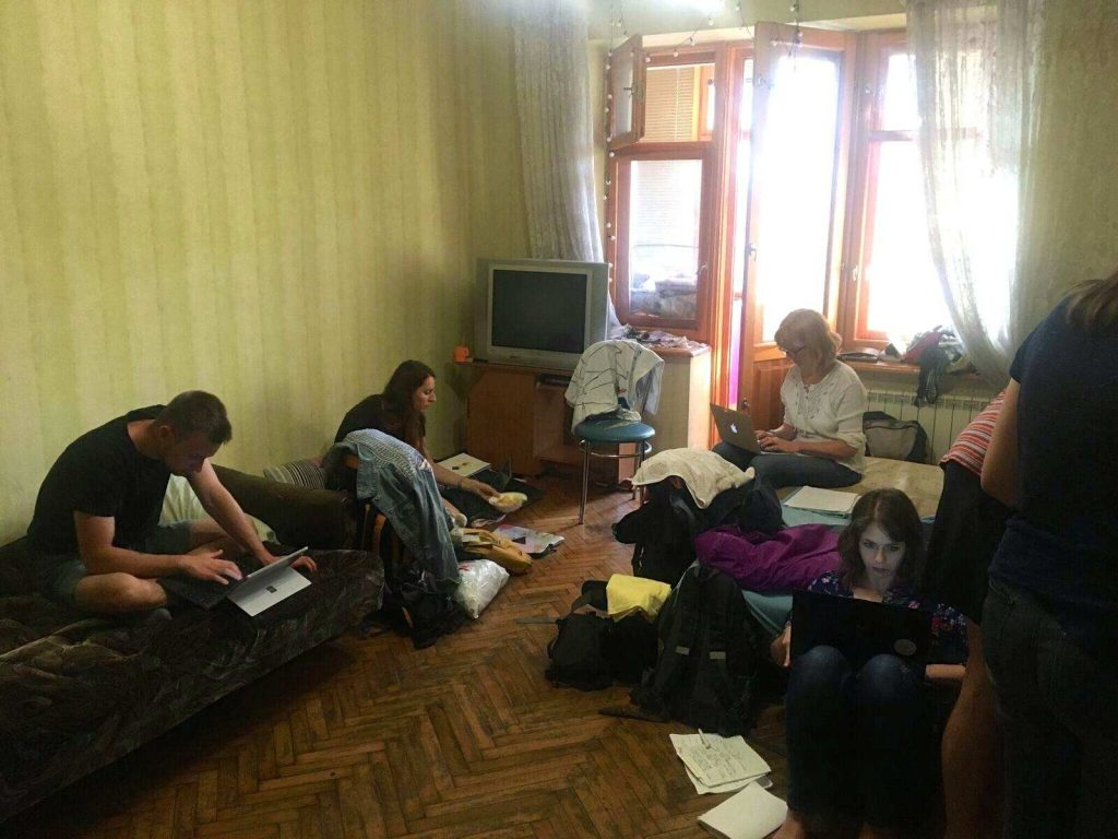 Huone, jossa neljä ihmistä istuu vuoteilla ja lattioilla tietokoneiden ja paperien kanssa.