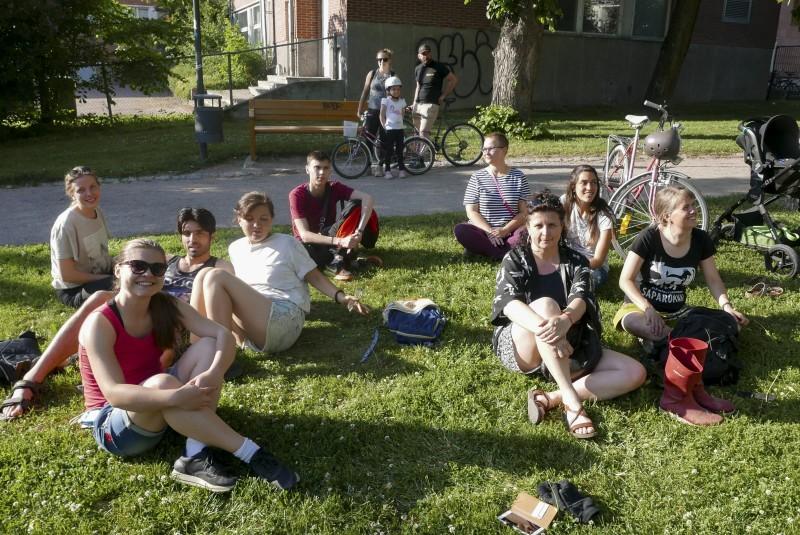 iloisia ihmisiä, ulkona, istuu nurmikolla