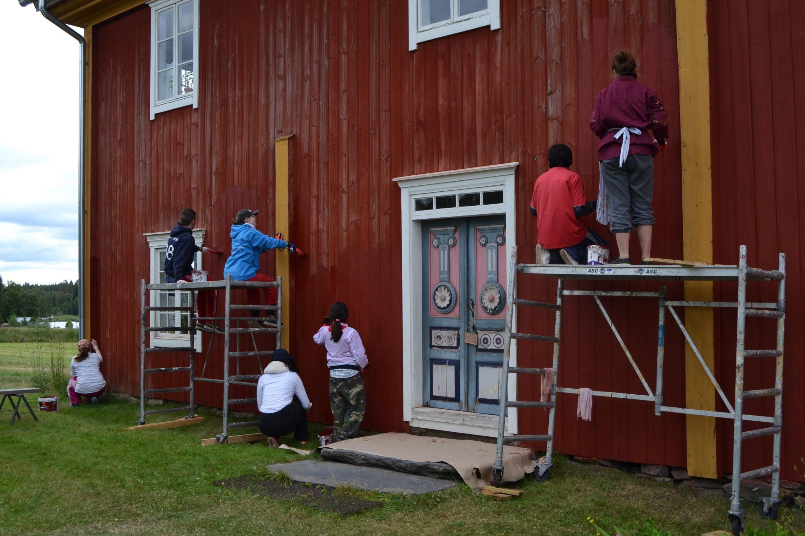 Ryhmä vapaaehtoisia maalaamassa vanhaa rakennusta