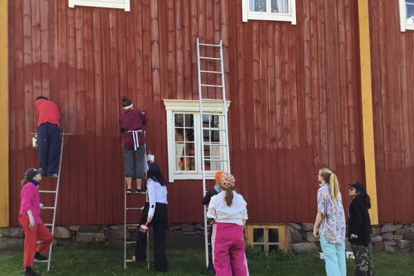 vapaaehtoiset tikkaiden kanssa maalaamassa taloa