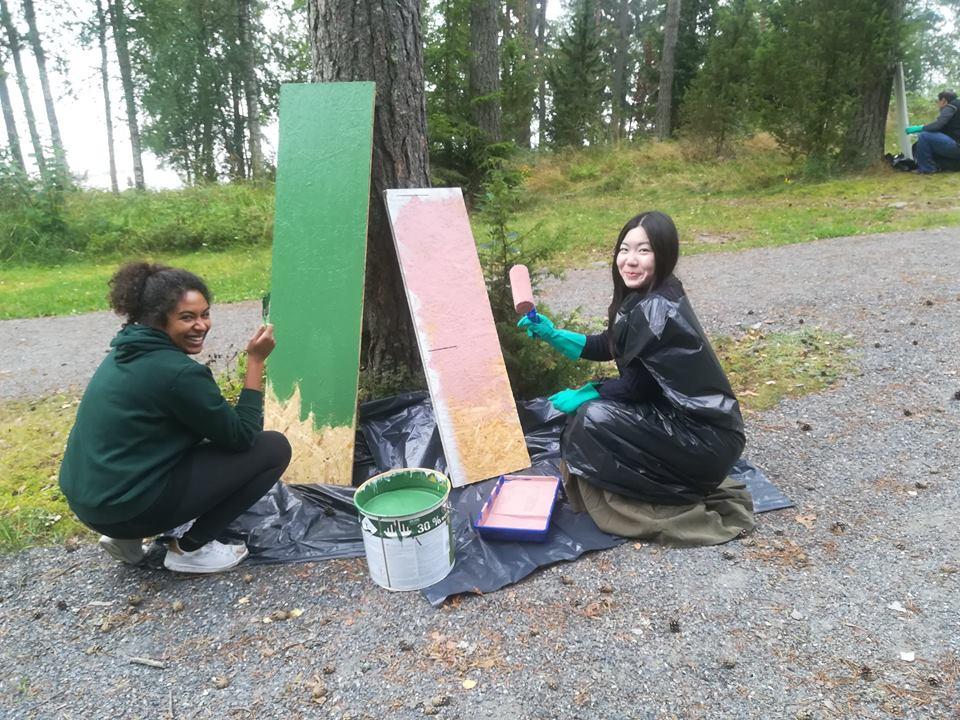kaksi ihmistä maalaamassa kylttejä