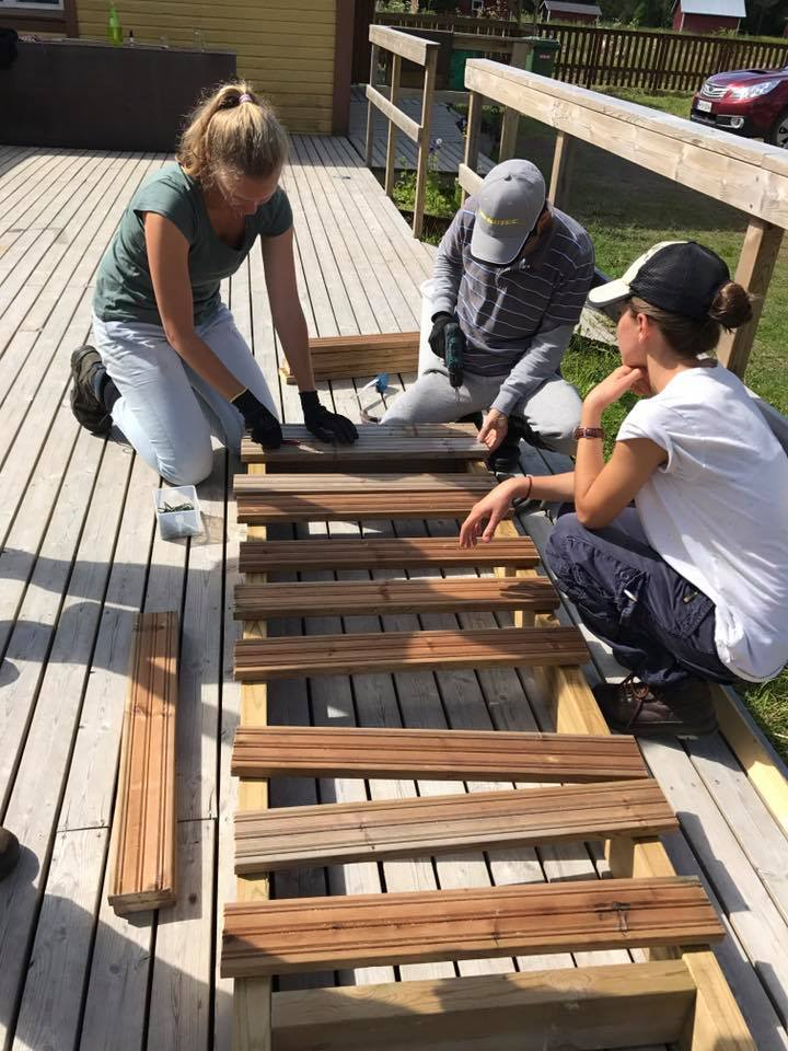 Kolme ihmistä rakentaa aitaa
