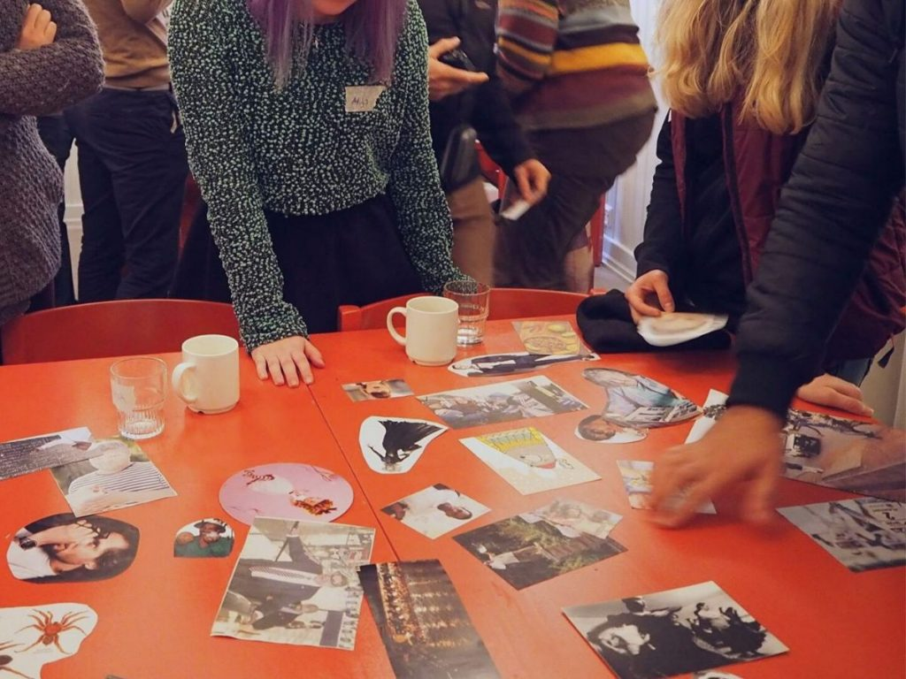 ihmiset katsomassa valokuvia pöydällä