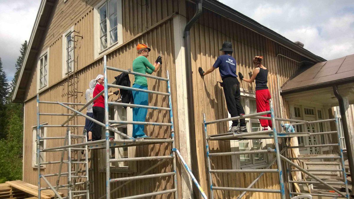 Ihmisiä rakennestelineillä maalaamassa taloa