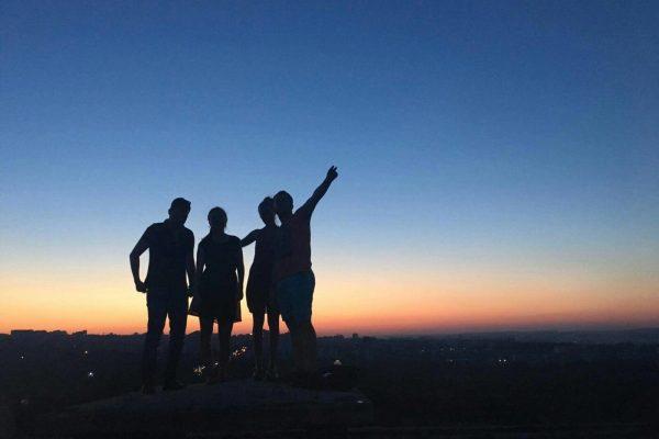 Neljä ihmistä seisoo vasten auringonlaskua
