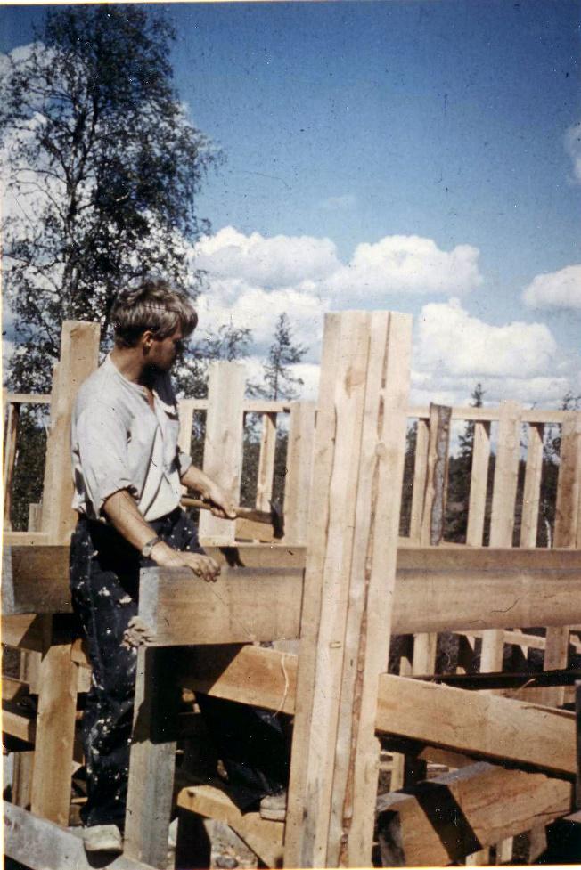 Nuori mies vasaran kanssa keskeneräisen rakennuksen vieressä