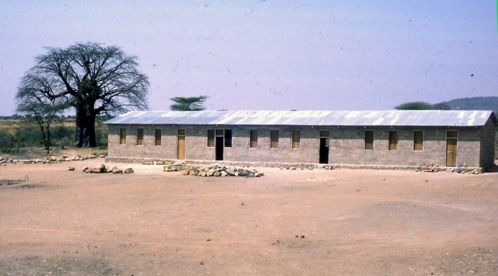 Tiilistä rakennettu peltikattoinen yksikerroksinen koulu.