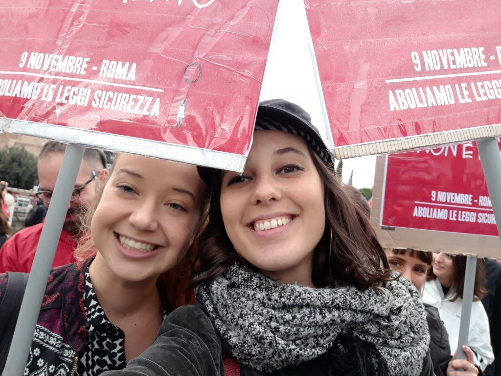Kaksi naista hymyilee mielenosoituskylttien takaa