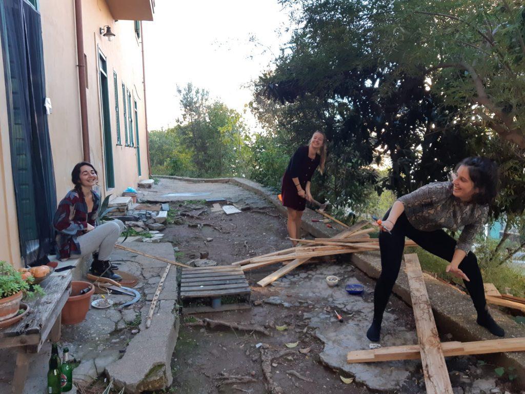 Kolme naista työkalujen ja laudanpätkien kanssa