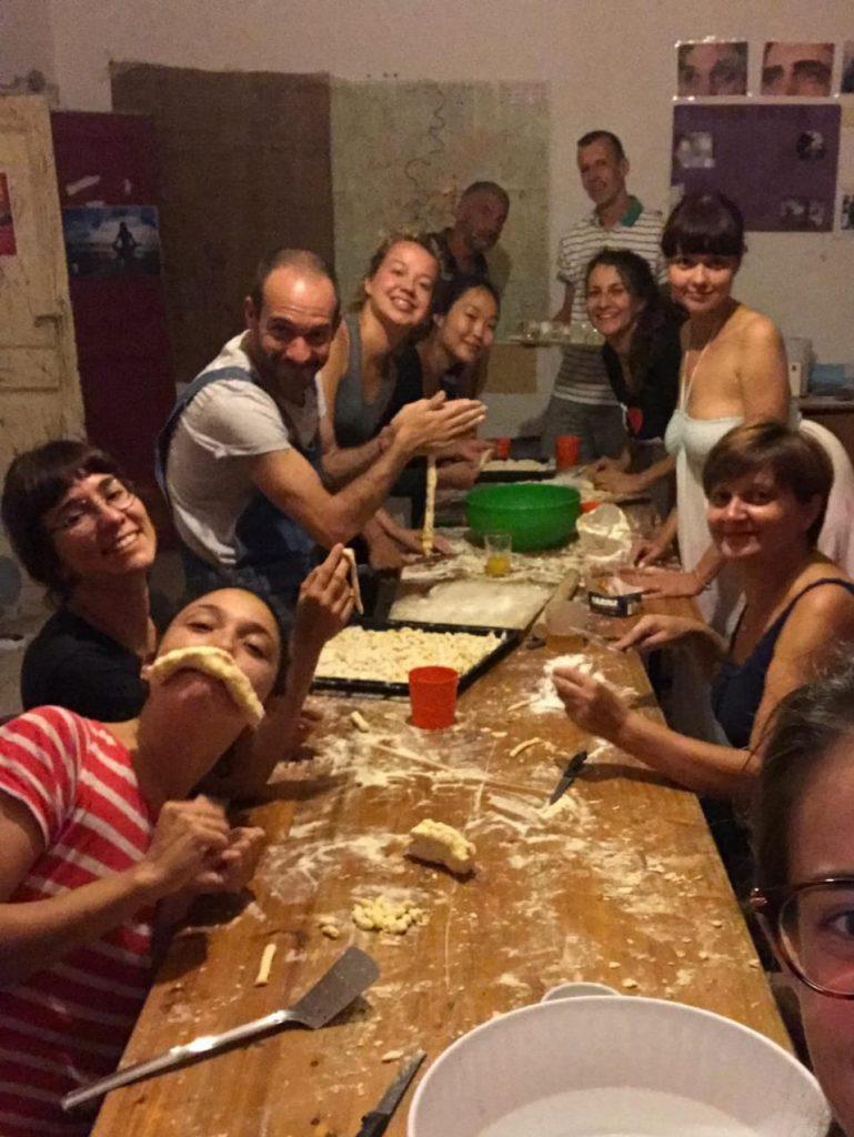 Ryhmä ihmisiä hassuttelee ruokapöydän ääressä leipoessaan