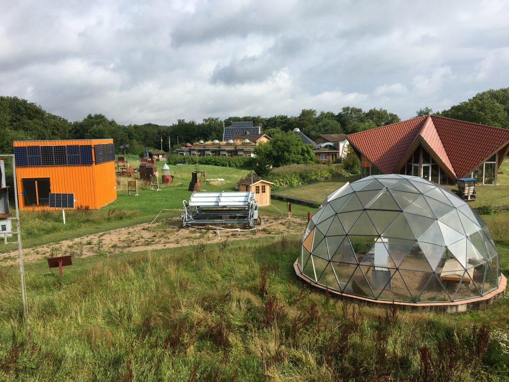 Useita rakennuksia, joissa aurinkopaneeleita, ja suuri lasikupu vihreällä nurmella
