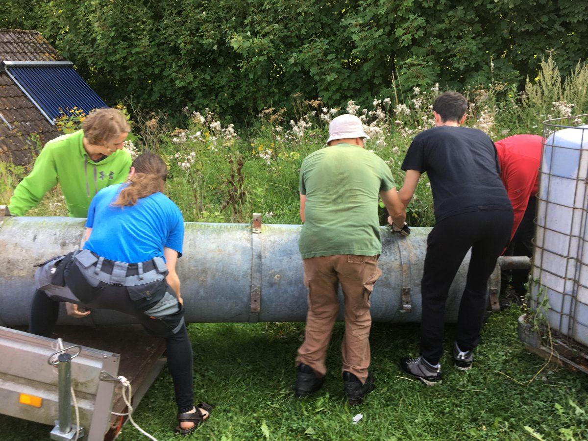 Ryhmä vapaaehtoisia kantaa isoa metalliputkea