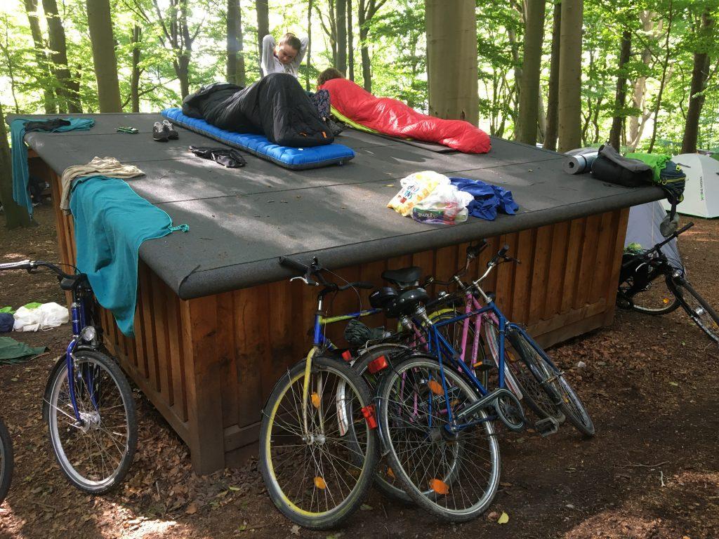 Laavu, polkupyöriä ja vapaaehtoisia makuupusseineen metsässä