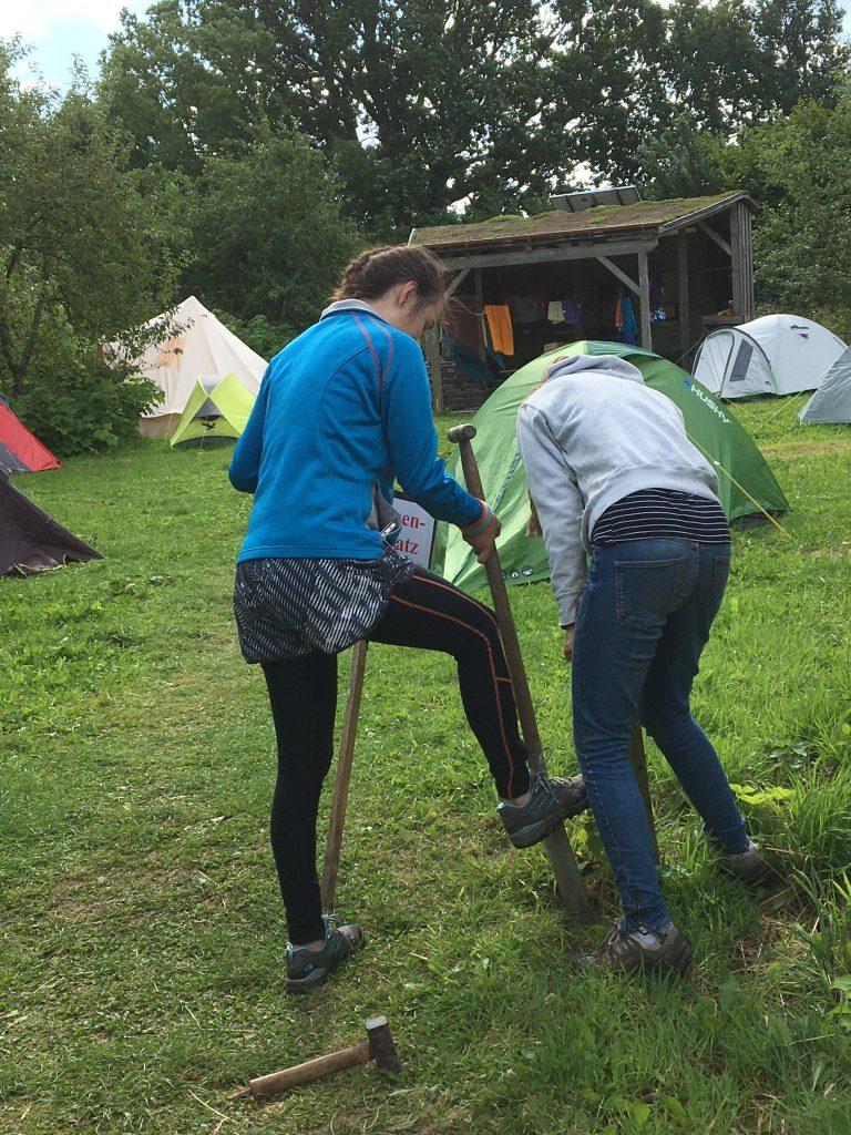 Kaksi ihmistä selin kameraan, taustalla useita telttoja pystytetty nurmelle